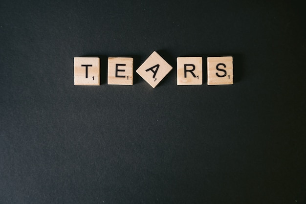 High angle shot of tears message on a black wall