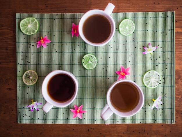 テーブルの上に置かれた白いマグカップで3つの異なる色合いの熱いお茶をハイアングルで撮影しました