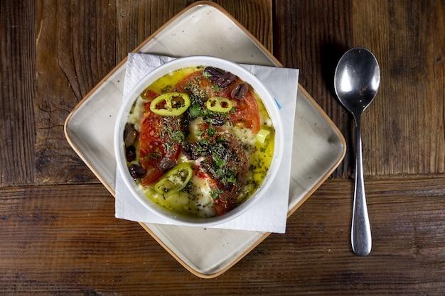 Colpo di alto angolo del piatto tradizionale con formaggio feta arrosto, peperone caldo, pomodoro e olio d'oliva