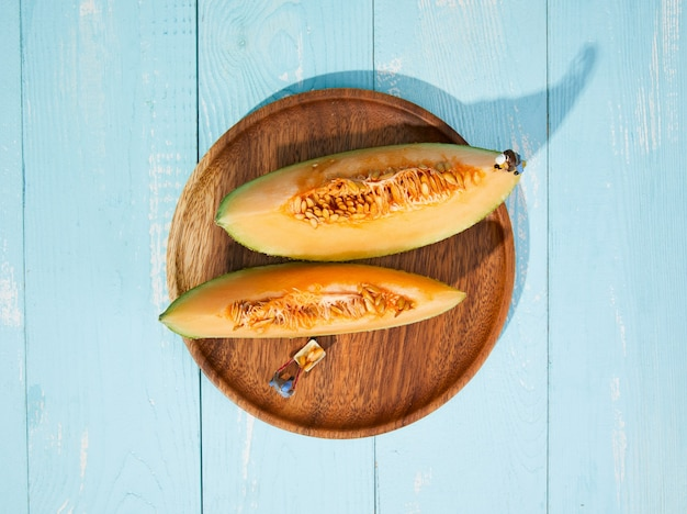 High angle shot of two slices of fresh melon on a wooden plate