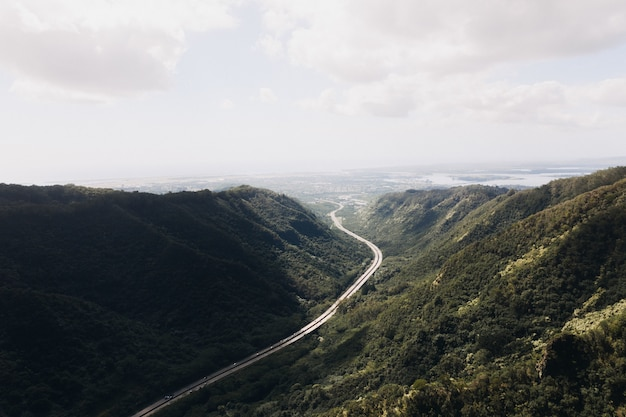 High angle shot of a valley road with a cloudy blue sky