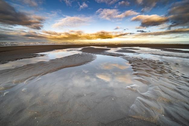 Colpo di alto angolo di pozzanghere d'acqua sulla riva con un cielo blu