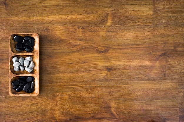 High angle shot of white and black rocks in a wooden plate on a wooden surface