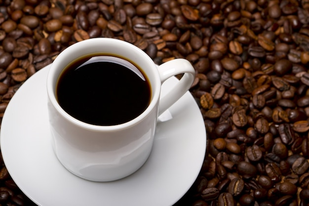High angle shot of a white cup of black coffee on a surface full of coffee beans