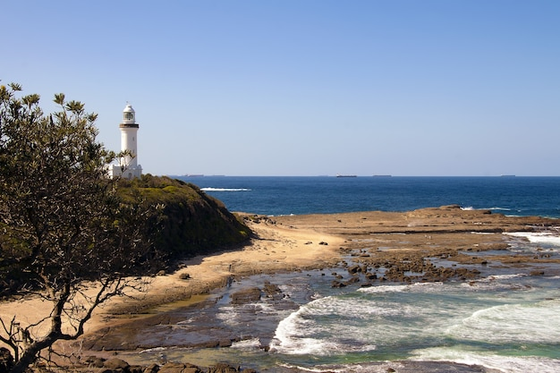 High angle shot of a white lighthouse on the shore of the sea