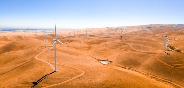 High angle shot of the wind turbines in a sandy field captured on a sunny day