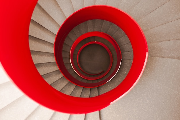 High angle shot of a winding staircase with a red railing