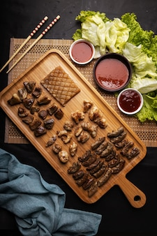 High angle shot of a wooden tray of fried meat, potatoes, vegetables, and sauce on a black table