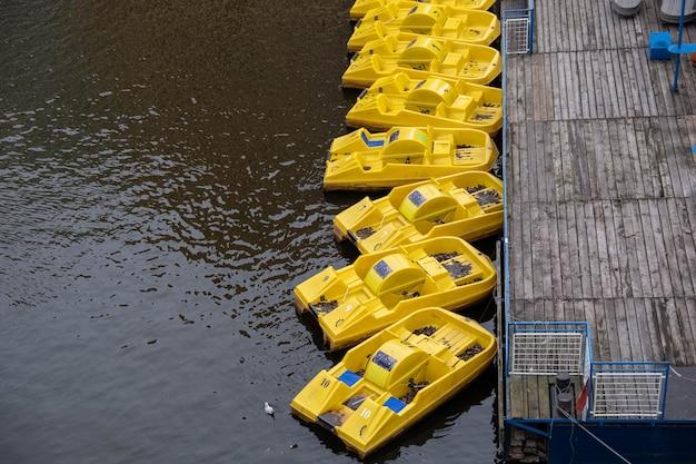 Colpo ad alto angolo delle barche a pedali gialle stanche al molo di legno sulla superficie calma dell'acqua