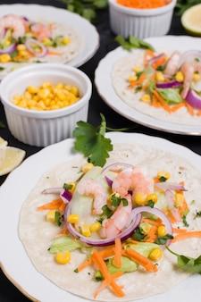 High angle of shrimp and other food on pita