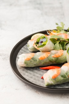 High angle of shrimp rolls on plate with sauce