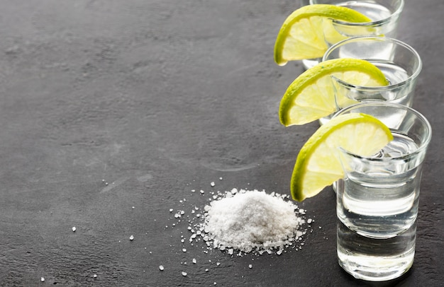 High angle silver tequila shots and lime slices with copy space