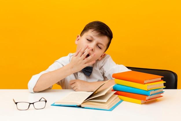 高角度の眠そうな少年の読書