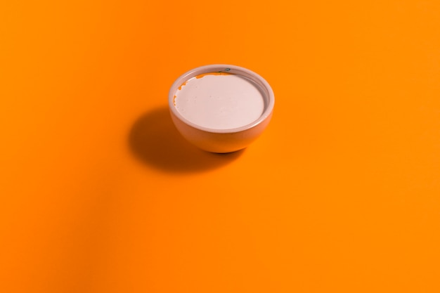 High angle small bowl with paint on orange background
