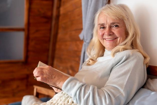High angle smiley elder woman reading