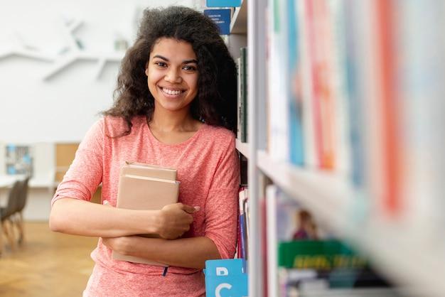 High angle smiley girl holding books