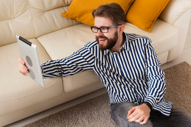 High angle of smiley man at home with tablet next to sofa