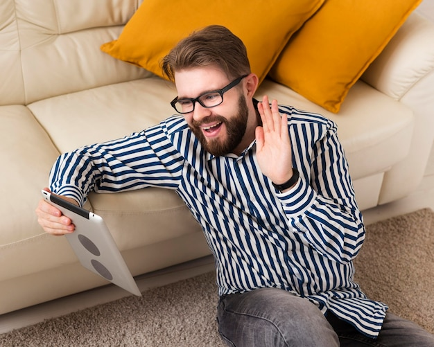 High angle of smiley man at home with tablet