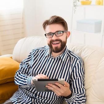 High angle of smiley man on sofa with tablet