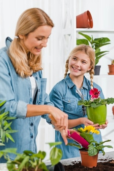 High angle smiley mother and daughter planting flowers