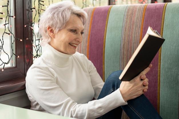 High angle smiley senior female reading