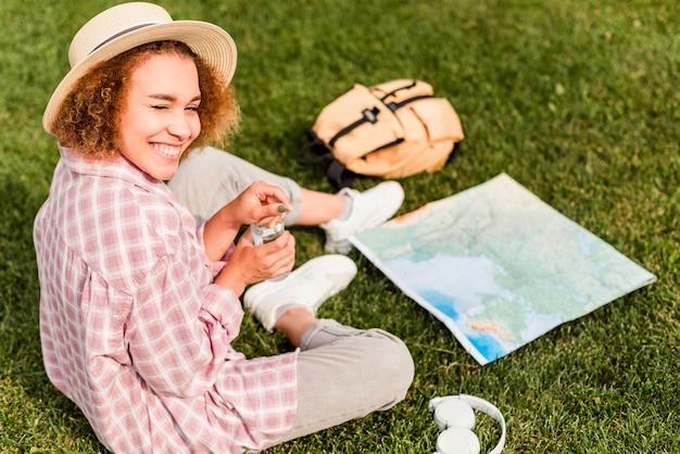 ハイアングルのスマイリー女性が新しい目的地の地図をチェック