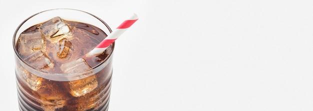 Alto angolo di soft drink in vetro con paglia e cubetti di ghiaccio