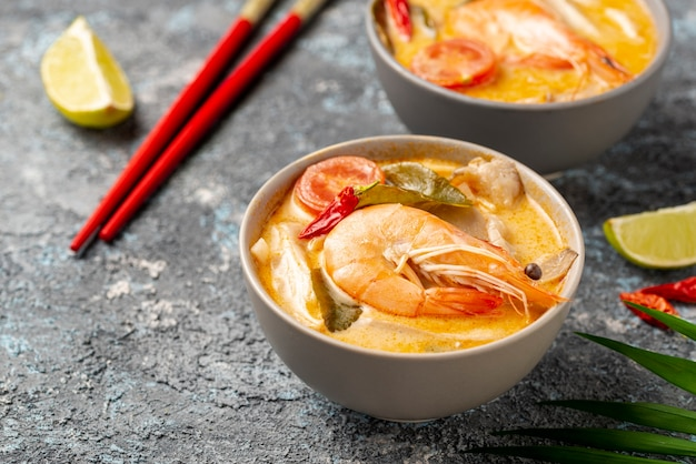 High angle soups in bowls with shrimp chopsticks and lemon