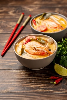 High angle soups in bowls with shrimp lemon and chopsticks