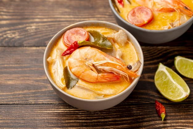 High angle soups in bowls with shrimp and lemon