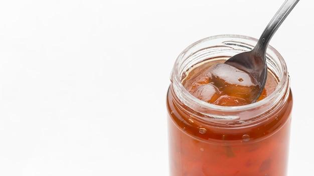 High angle spoon in jam jar