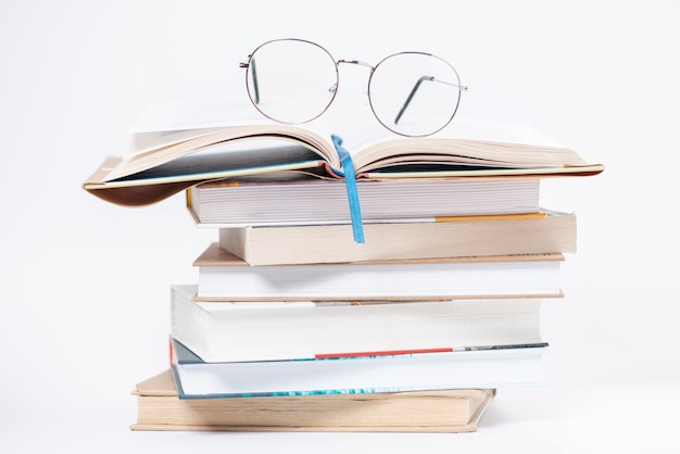 High angle stack of books with glasses on top