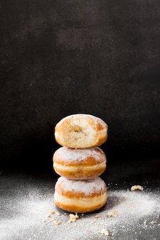 High angle of stacked donuts with powdered sugar