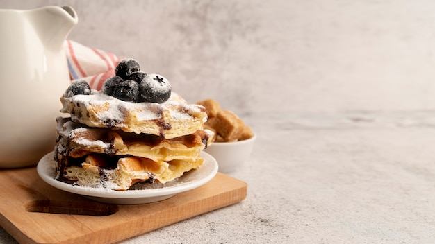 High angle of stacked waffles on plate with powdered sugar and chocolate sauce