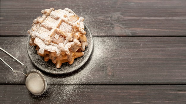 High angle of stacked waffles on plate with powdered sugar and copy space