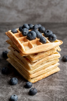 High angle of stacked waffles with blueberries on top