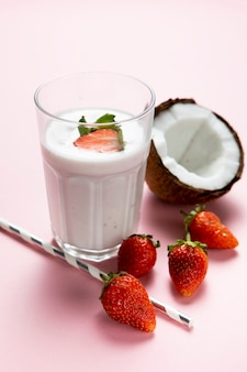 High angle of stawberry and milk glass on plain background