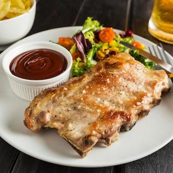 Alto angolo di bistecca sul piatto con birra e salsa