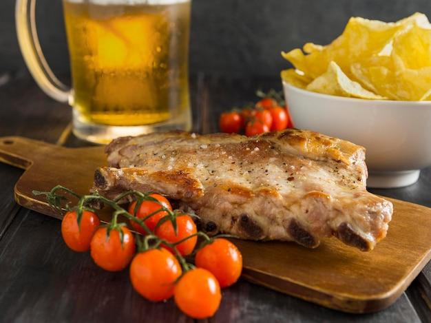 Alto angolo di bistecca con birra e pomodori