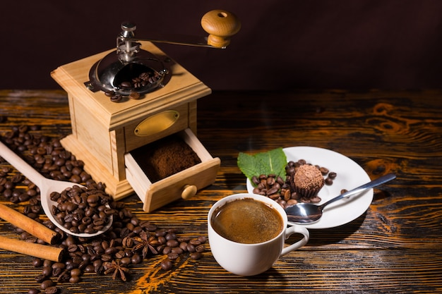 High angle still life of cup of hot brewed coffee on rustic wooden table with roasted coffee beans beside hand grinder and small plate with dessert truffle