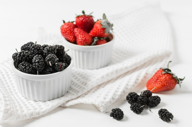 High angle of strawberries and mulberries in bowls
