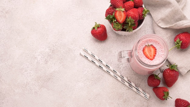 High angle of strawberry milkshake with copy space and straws