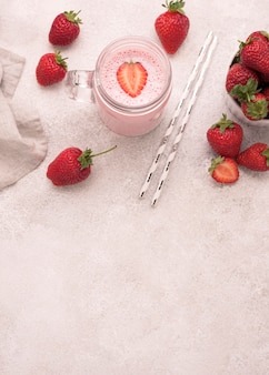 High angle of strawberry milkshake with straws and copy space