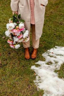 Alto angolo di donna alla moda che tiene il mazzo di fiori all'aperto in primavera