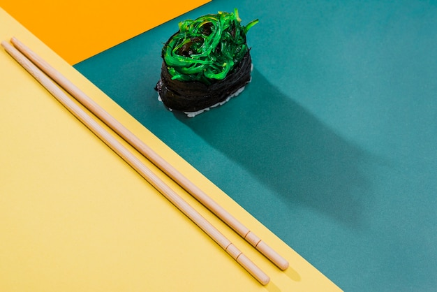 High angle sushi roll beside chopsticks
