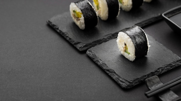 High angle of sushi rolls on slate with copy space