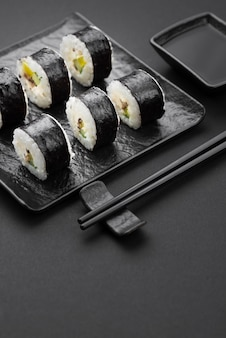 High angle of sushi rolls with chopsticks and sauce