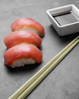 Sushi ad alto angolo con bastoncini e salsa