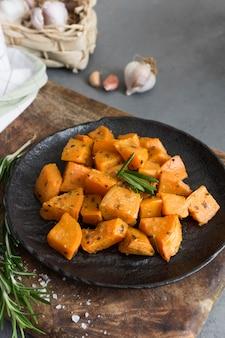 Высокий угол сладкий картофель на черной тарелке