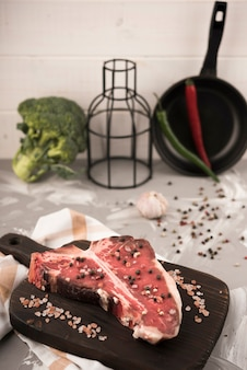 Высокий угол стейк на косточке и ингредиенты на кухне